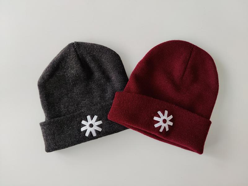 A gray beanie with a white star that has eight points and a red beanie with a white star that has eight points